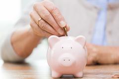 senior woman hand putting money to piggy bank - stock photo