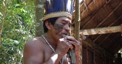 Native Brazilian playing wooden flute at an indigenous tribe in the Amazon Stock Footage