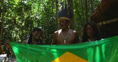 Native Brazilians showing the Brazilian Flag at tribe in the Amazon Stock Footage