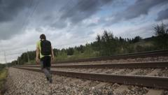 Man walking back and forth on the side of a train track Stock Footage