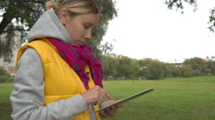 Woman in yellow vest using tablet pc in the park - stock footage