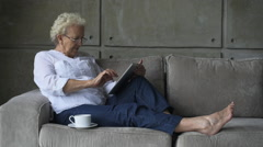 Little old granny working with digital tablet Stock Footage