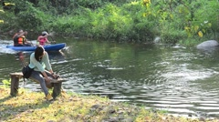 Thai women sit on  bench and traveler paddle kayak or canoe at Suan Phueng Stock Footage