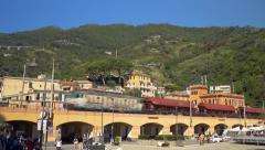 Freight train on the bridge passes an local village. - stock footage