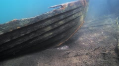Nose of a sunken rowboat with sunbeams - stock footage