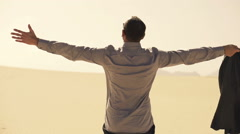 Young businessman with wide open arms on desert enjoying sunny day, slow motion Stock Footage