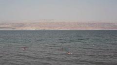 People float on water in sunny desert Dead Sea, Israel, Palestine - stock footage