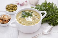 A delicious pea cream with aromatic spices on a wooden table. - stock photo