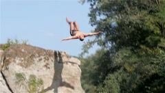 Young man jumping back flip from big rock on legs, tracking shot, slow motion. - stock footage