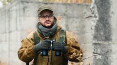 Man in camouflage looking through binoculars Stock Footage