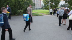 Parents with beautiful first former schoolkids walk to the school yard Stock Footage