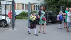 Mother and beautiful first former schoolgirl walk to the school yard, Russia - stock footage