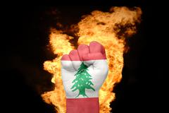 fire fist with the national flag of lebanon - stock photo