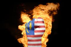 fire fist with the national flag of malaysia - stock photo