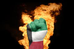fire fist with the national flag of kuwait - stock photo