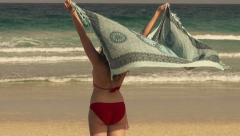Young woman in bikini standing on beach with stretched pareo, slow motion shot a Stock Footage