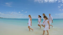 Smiling Caucasian family walking barefoot on the beach - stock footage