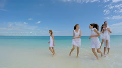 Caucasian family wearing white clothes barefoot on the beach - stock footage