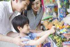 Parents and son buying toys Stock Photos