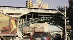 Truck and cars driving under elevated 1 subway train track 125th Street Harlem Stock Footage