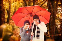 Composite image of mature couple blowing their noses under umbrella - stock photo