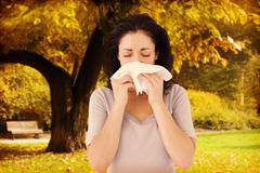 Stock Photo of Composite image of sick brunette blowing her nose