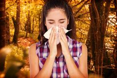 Composite image of beautiful woman sneezing in a tissue Stock Photos