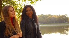 Friends,  girls, caucasian and african walking in park by pond, slow motion. Stock Footage