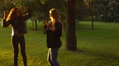 Two friends,  girls, caucasian and african walking in park, slow motion. Stock Footage