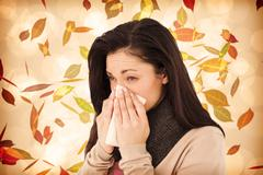 Composite image of sick brunette blowing her nose Stock Photos