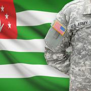 American soldier with flag on background - Abkhazia - stock photo