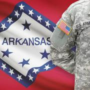 American soldier with US state flag on background - Arkansas - stock photo