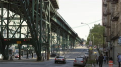 Buses cross each other on 125th St in Harlem under elevated subway train station Stock Footage