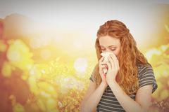 Composite image of sick blonde woman blowing her nose - stock photo