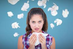 Composite image of portrait of sick woman sneezing in a tissue Stock Photos