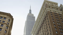 Empire State Building tilting down to NYPD police officer Herald Square NYC 4K - stock footage