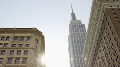 Sun shining on Empire State Building police officers in Herald Square NYC Stock Footage