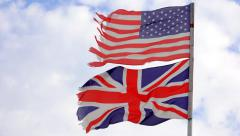 Old torn UK and american flags waving on blue sky Stock Footage