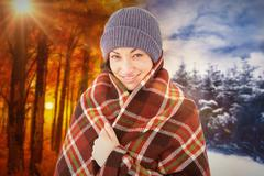 Stock Photo of Composite image of smiling brunette with checked blanket