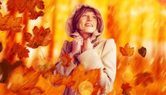 Composite image of smiling beautiful woman in winter coat looking up Stock Photos
