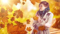 Composite image of thoughtful woman in winter coat Stock Photos