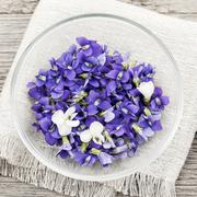 Edible violets in bowl - stock photo