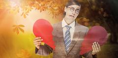Composite image of geeky businessman crying and holding broken heart card Stock Photos