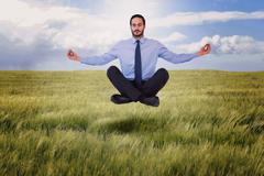 Composite image of businessman in suit sitting in lotus pose Stock Photos
