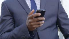 Businessman Using Mobile Phone: African american businessman sending email Stock Footage