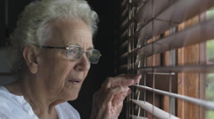 Old lady eldery granny woman window look surprise Stock Footage