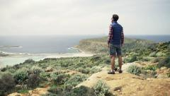 Young man hiking hill and admire view on Balos bay in Crete Stock Footage