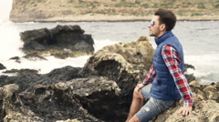 Young man relaxing on rocks and admire view - stock footage