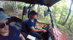 A family riding in side by side four wheeler in thick forest Stock Footage
