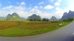 Slow motion ride through mountainous countryside with people planting rice. Stock Footage